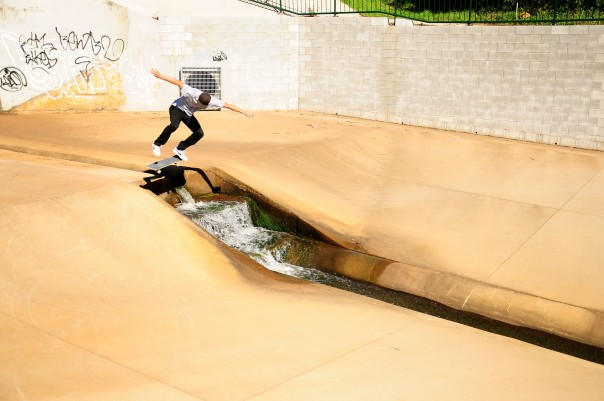Jarrod kickflips over a water ditch